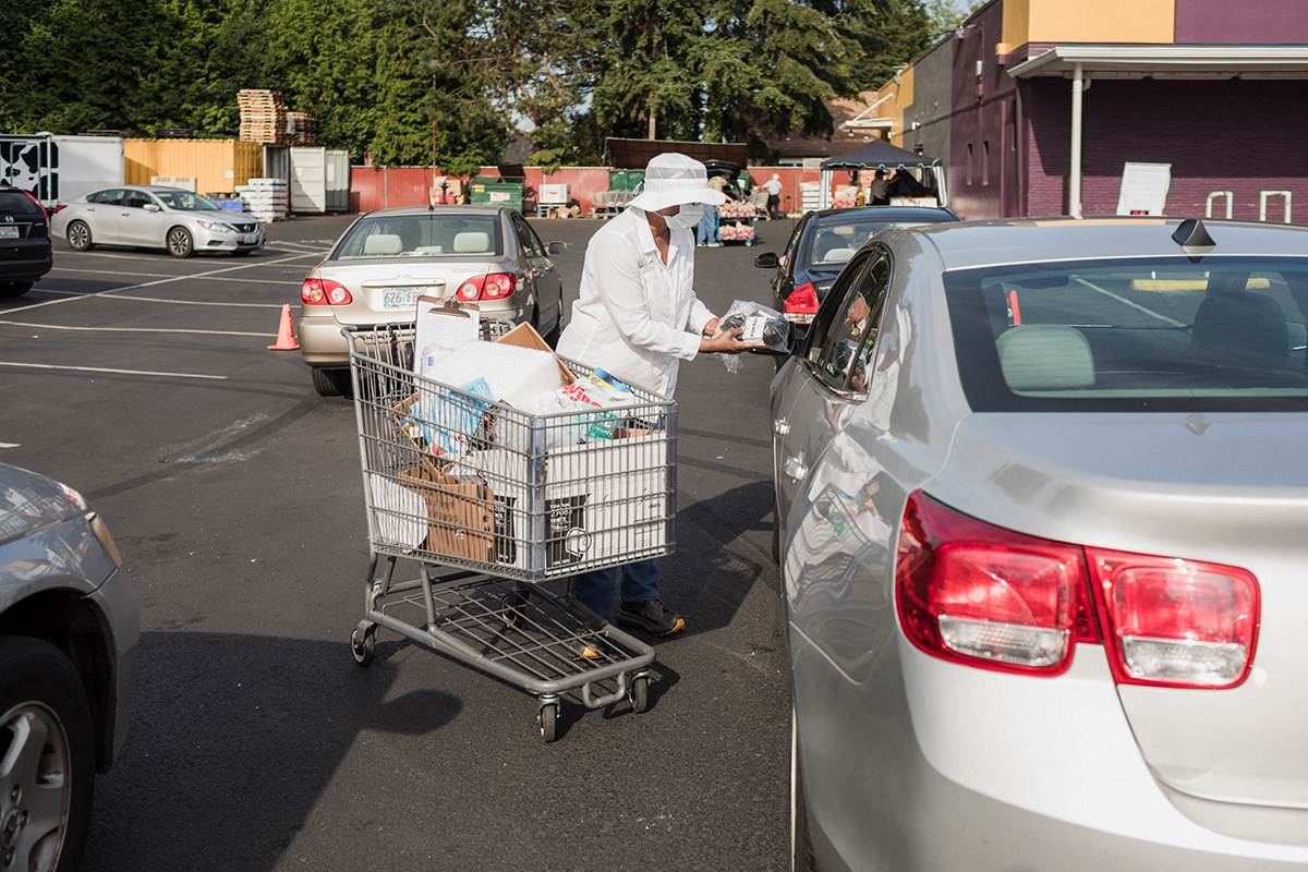 Traci White delivers pharmacy supplies to customers in cars at the Portland Adventist Community Services pantry