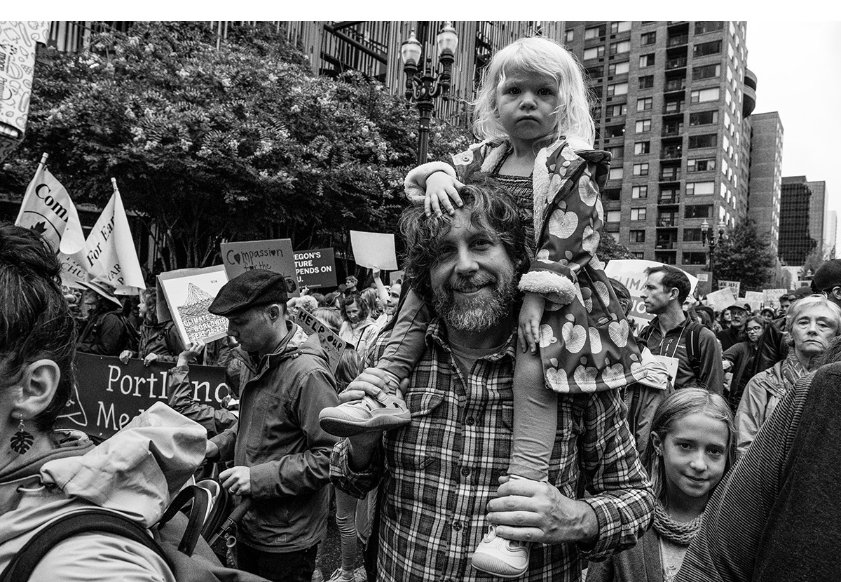 Portland Climate Strike: A child rides on the shoulders of an adult.