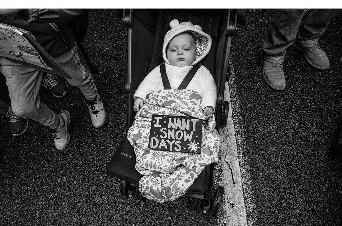 "Portland Climate Strike: A sign that reads ""I want snow days"" rests on a baby."