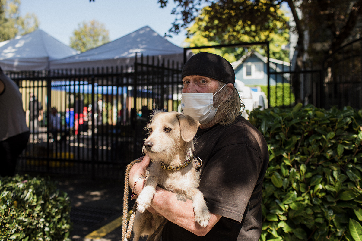 Michael Venso waits in the customer intake line at the William Temple pantry with his dog, Bugsy.