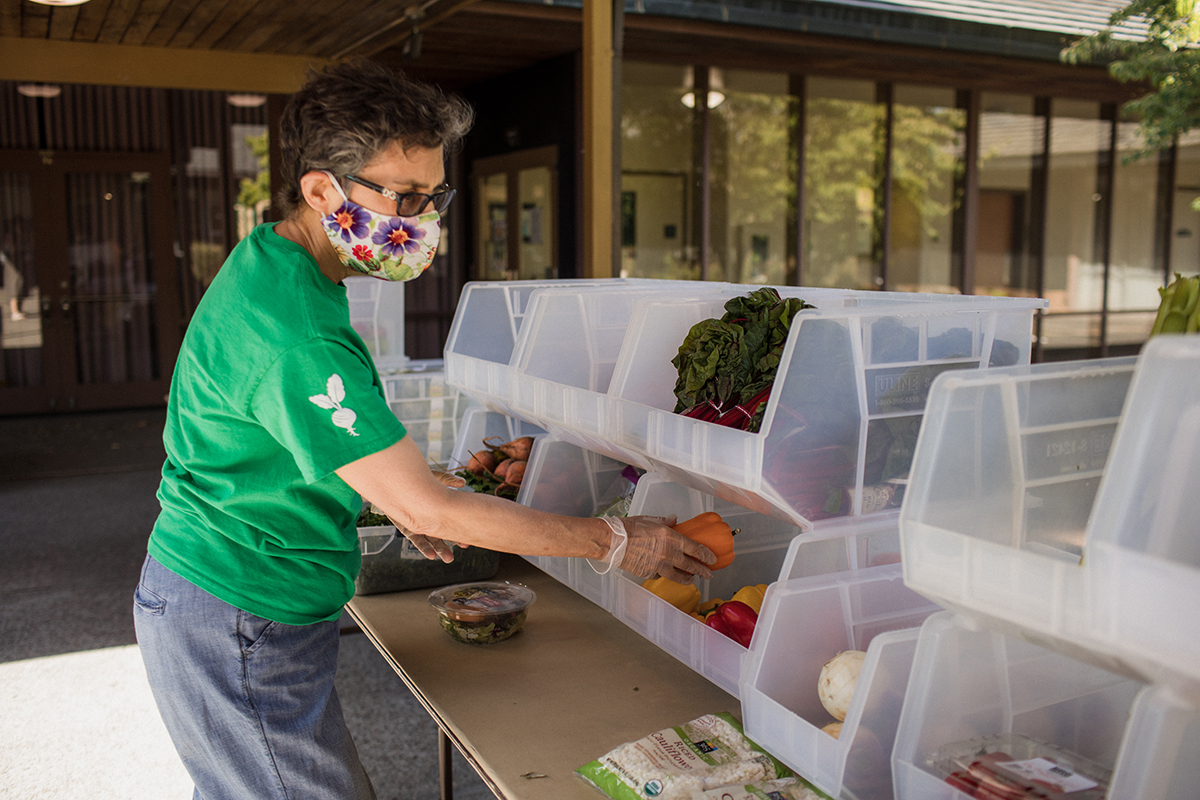 Volunteer Susan restocks produce in the shopping section of Lift UP's pantry.