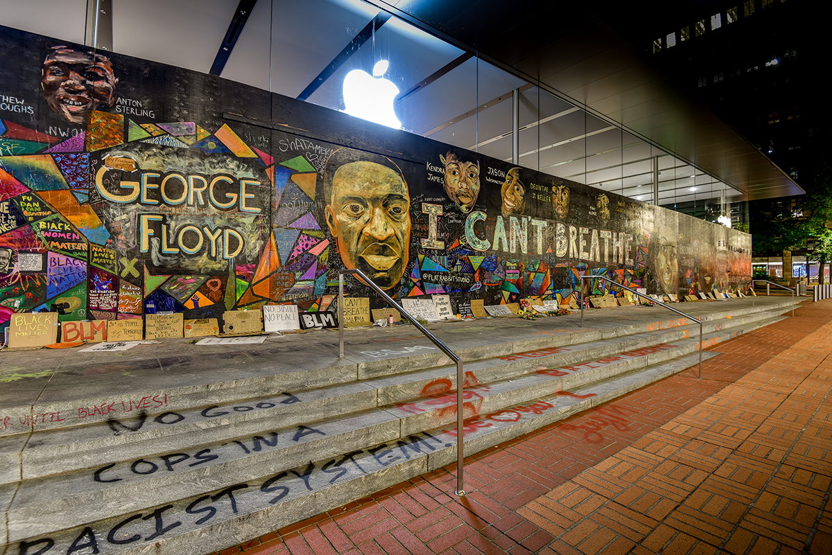 "A mural that pays tribute to George Floyd and others says ""I can't breathe."" The steps leading the sidewalk in front of the mural features graffiti supporting Black Lives Matter."
