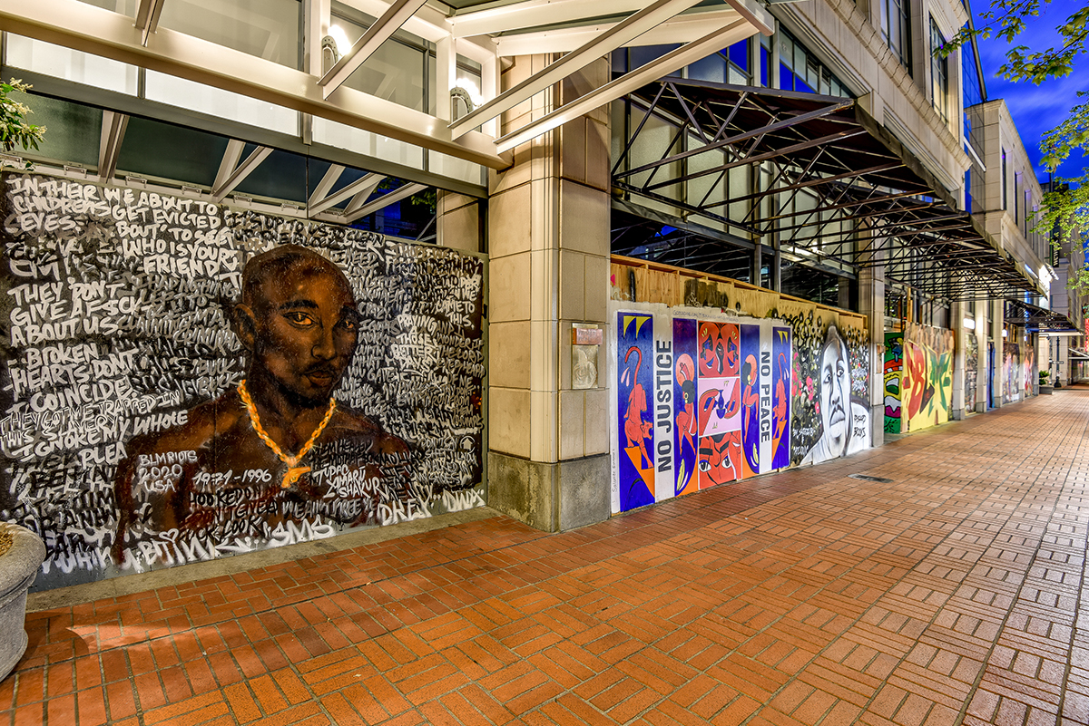 "A mural features an image of Tupac Shakur. Beside it is a mural that says ""No Justice No Peace."""