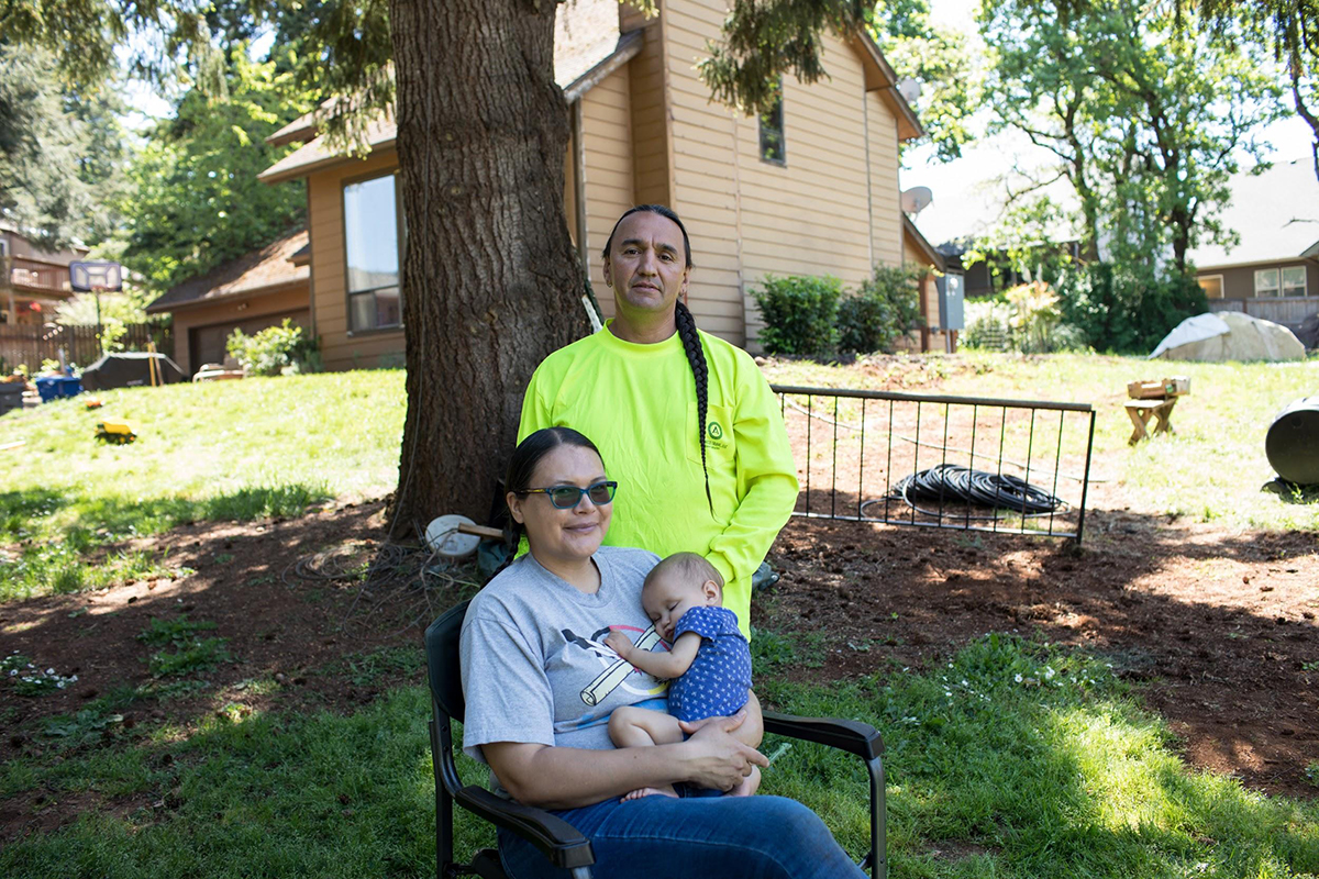 Leon Araiza outside his home with his wife and baby