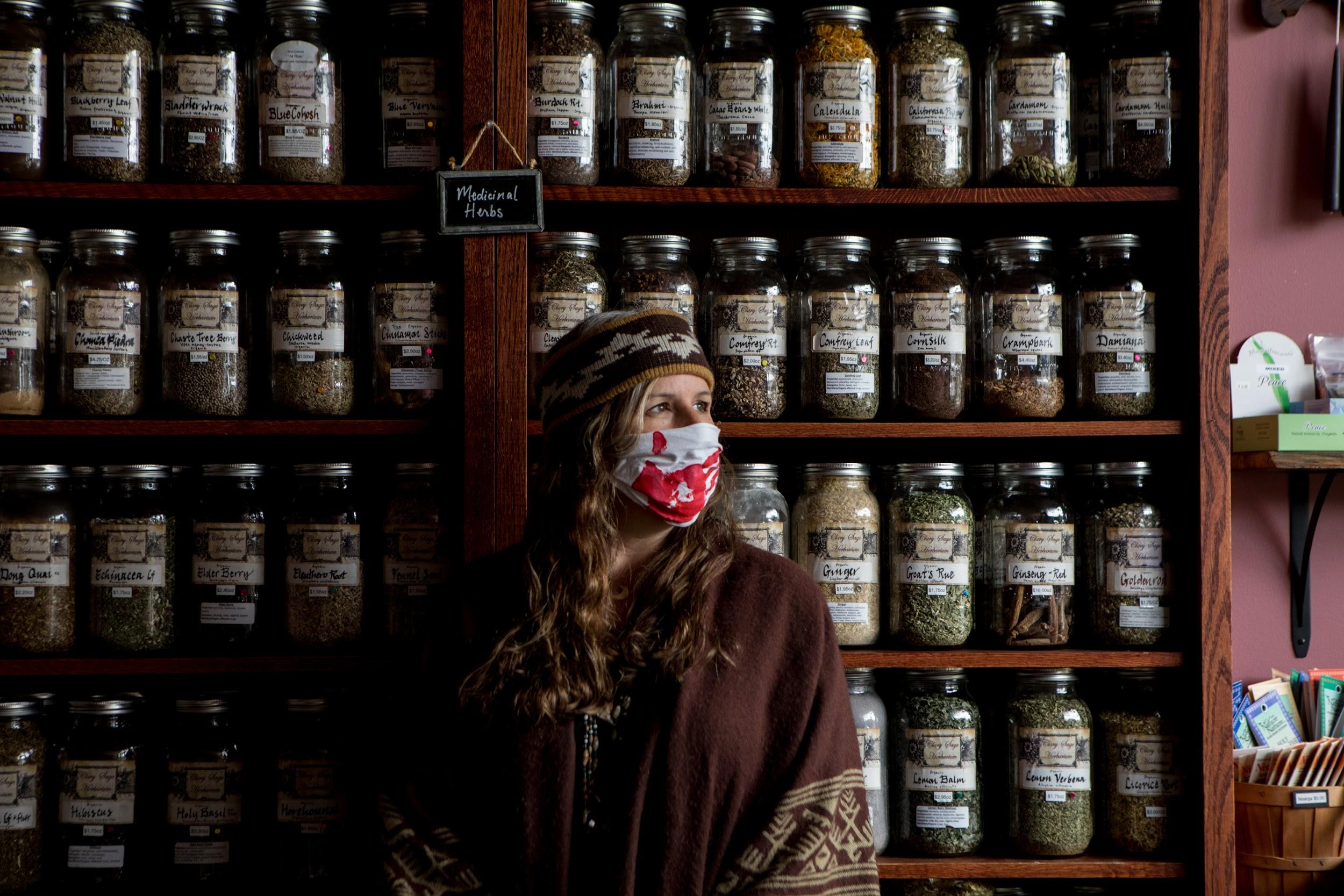 Laurie Books wears a mask inside Clary Sage Herbarium