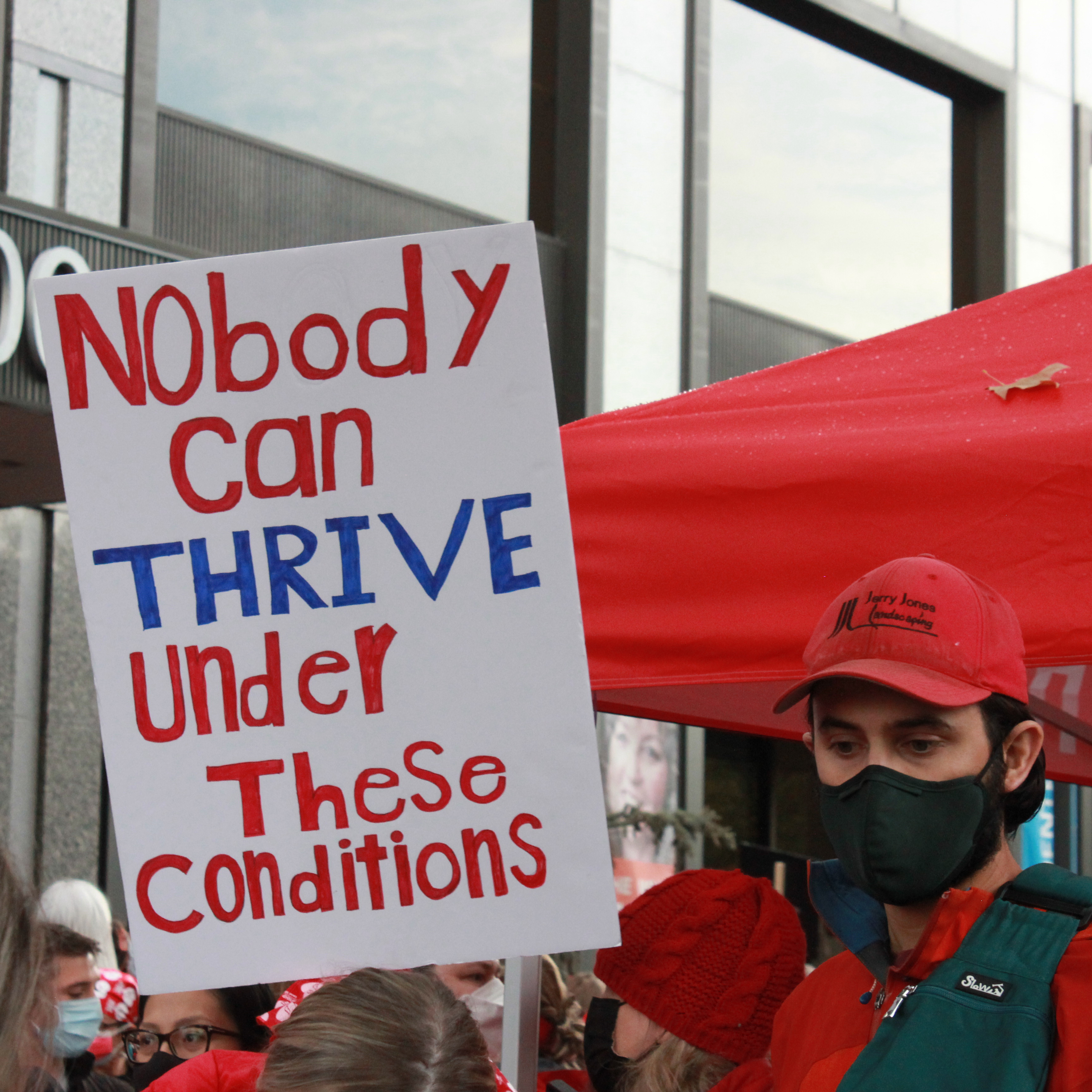 """Photo of a person holding a sign that reads """"nobody can thrive under these conditions"""" at a rally for Kaiser Permanente workers"""