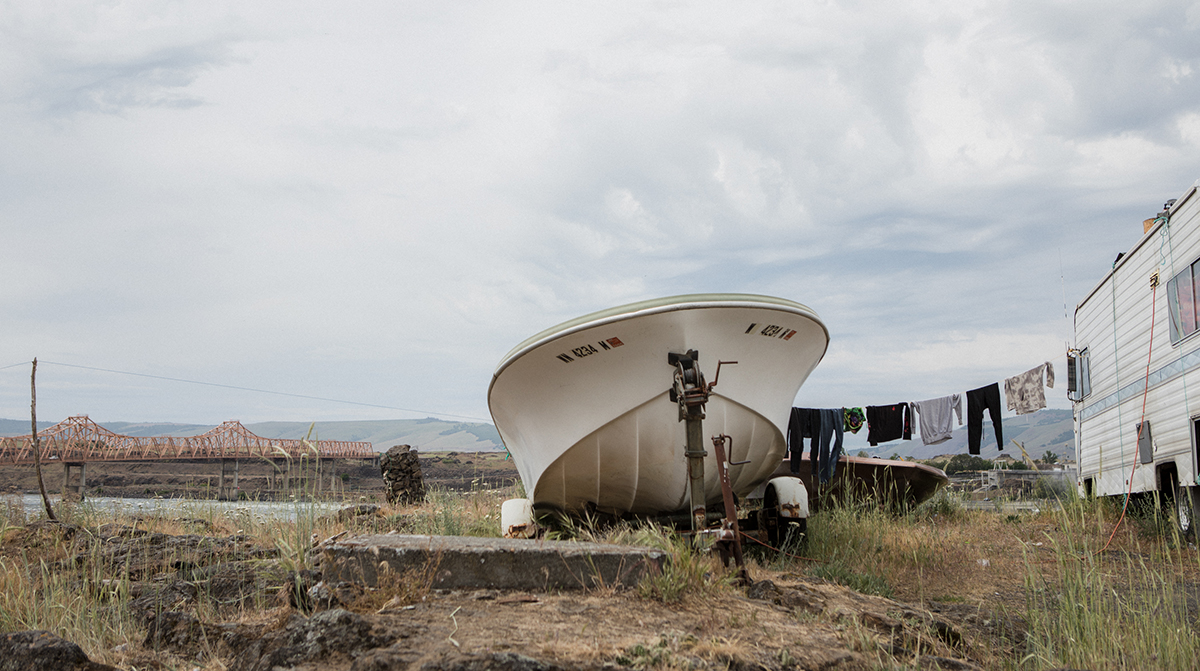 A fishing boat is docked outside a mobile home