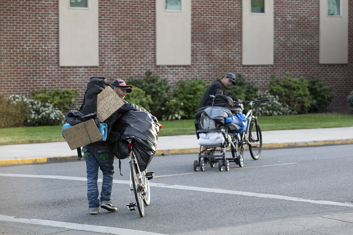 Two men with their belongings on bicycles