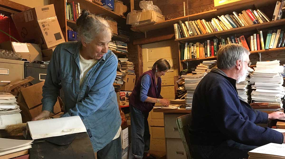 Three people look through papers in an office full of documents