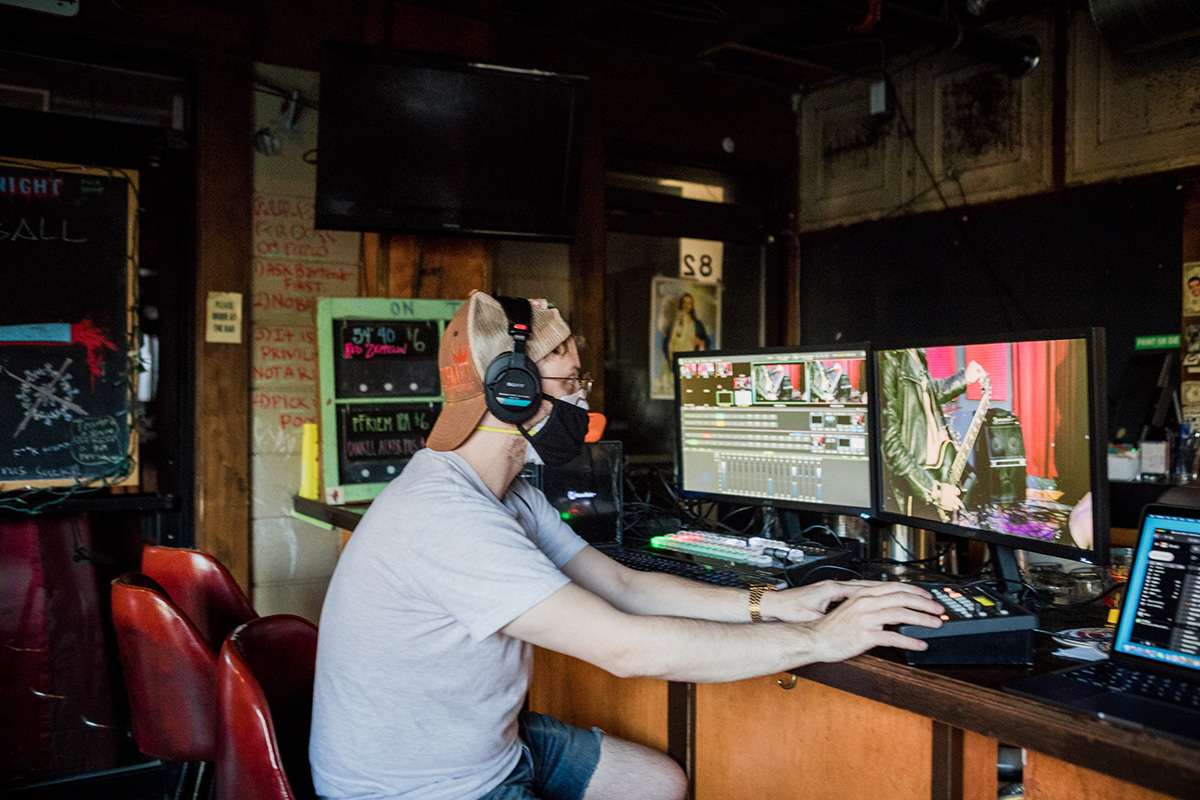 Chase Spross uses digital equipment, wearing headphones and a protective mask
