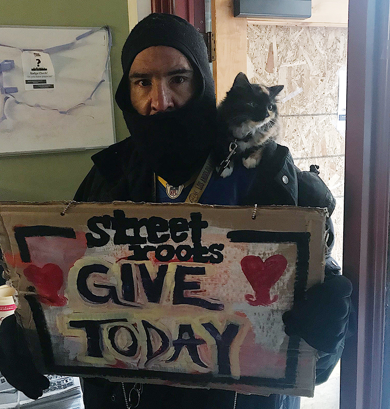 Corey Mency stands with his cat on his shoulder, holding a sign that reads: Street Roots Give Today
