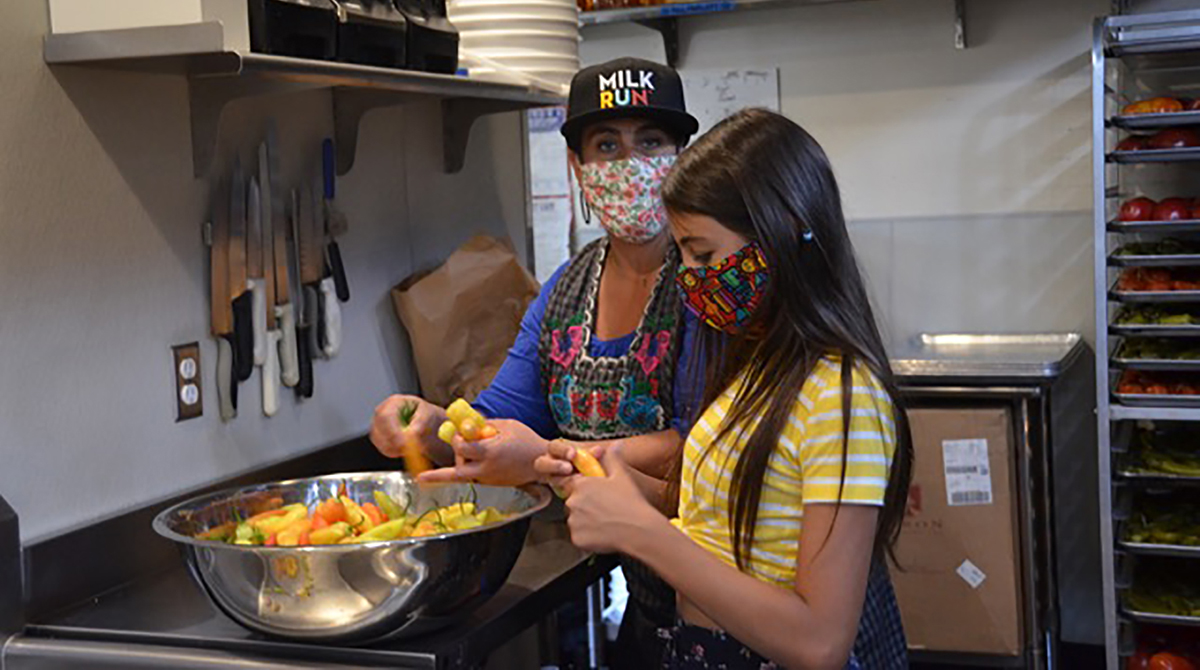 Chavela and Nikki Guerrero work with peppers in a commercial kitchen