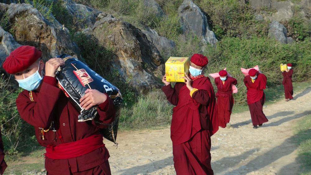 Nuns carry supplies