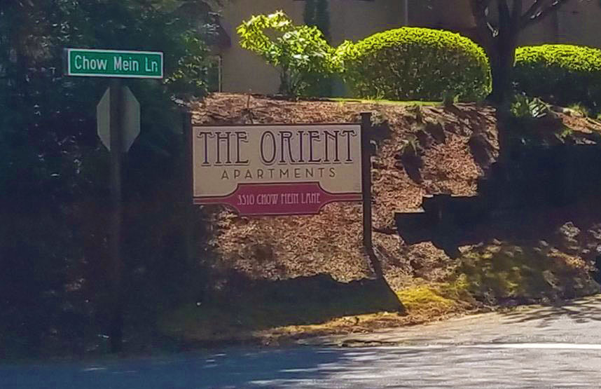 The Orient Apartments is seen beside a road sign that says Chow Mein Lane
