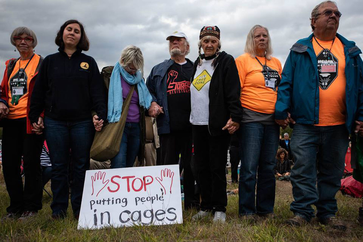 Protesters stand with a sign that reads: Stop putting people in cages