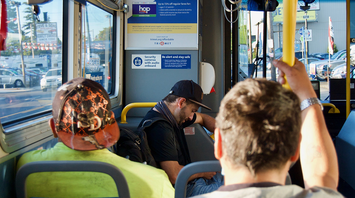 Riders sit on the bus, one of whom is not wearing a mask