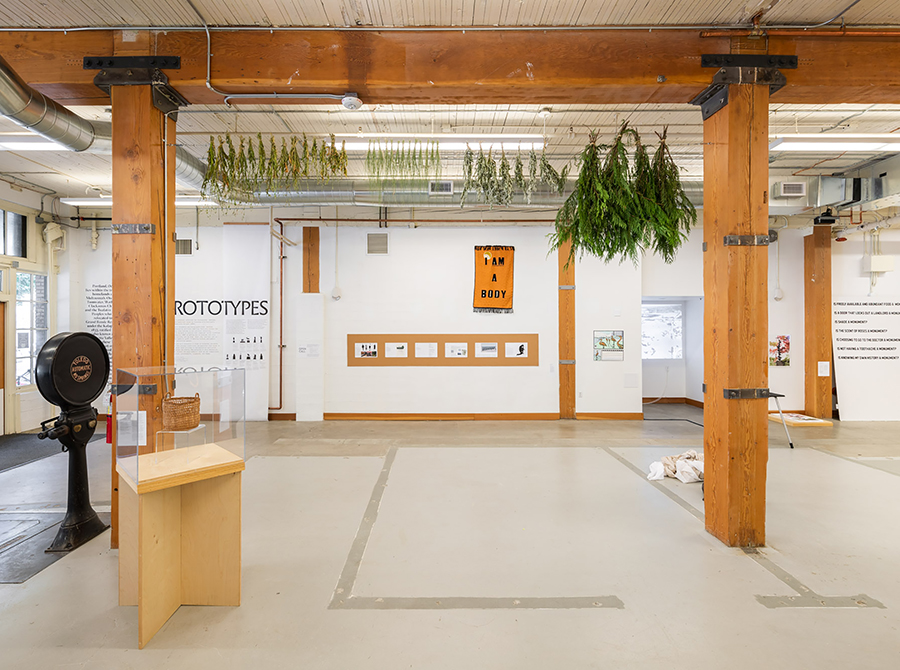 A photo of Sara Siestreem's work that hangs from the ceiling of the exhibit with ceremonial tobacco, sweet grass, mugwort and red cedar.