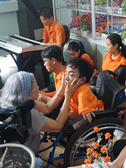 Tran To Nga touches the face and looks into the eyes of a person with physical deformities who sits in a wheelchair