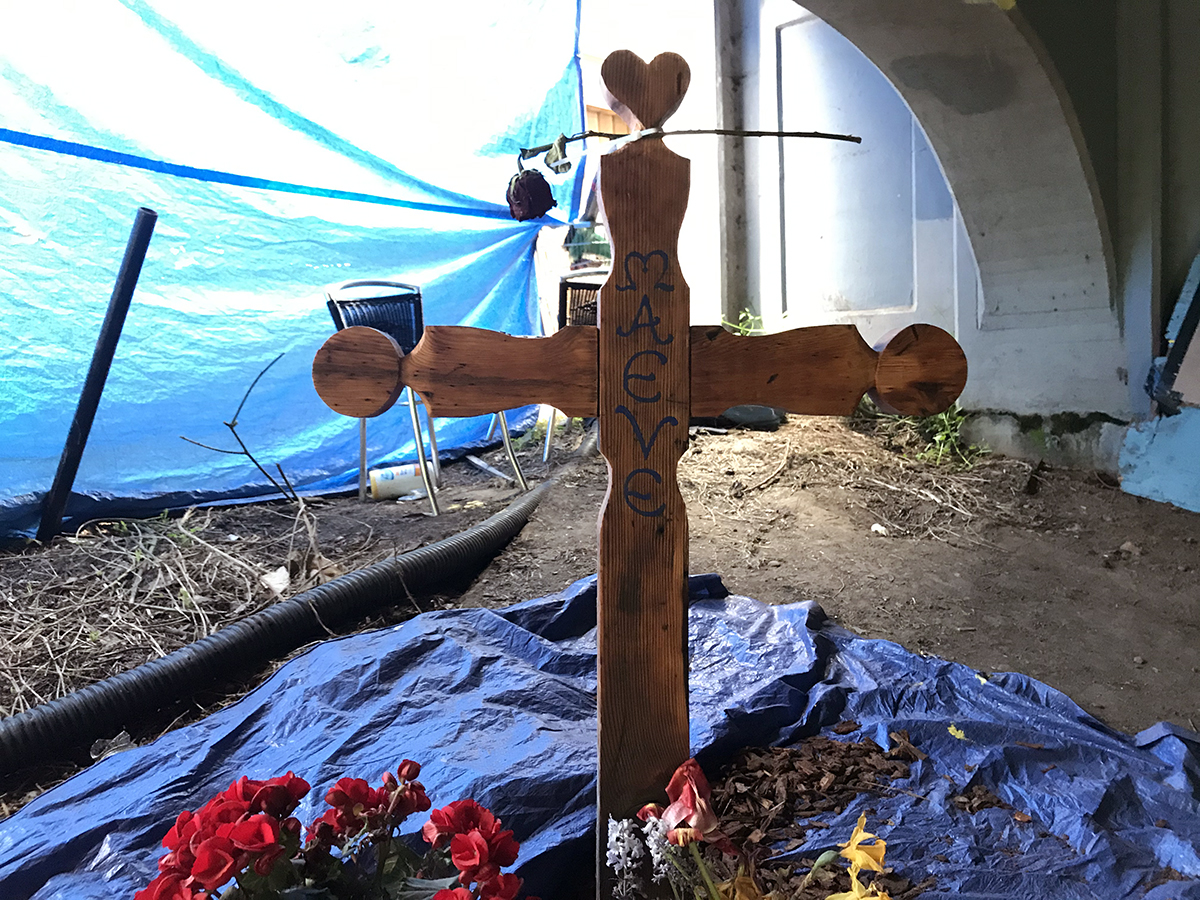 A cross made of wood says Maeve, with flowers beneath it