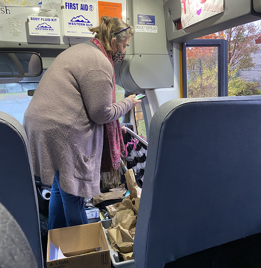 Trisha Olson on the bus with boxes of sack lunches and school work