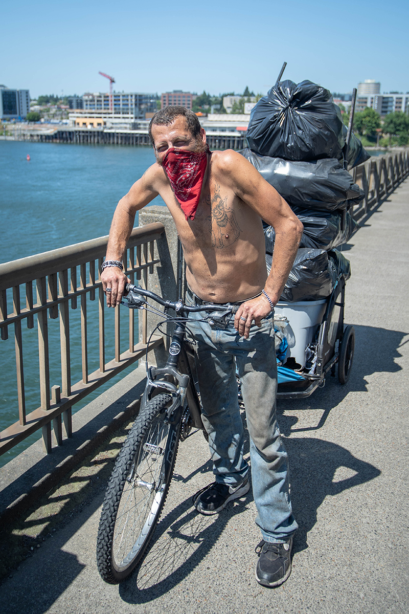 A man with a bandana covering his face sits stands on a bridge with his bicycle, which pulls a cart filled with bags of recyclables.