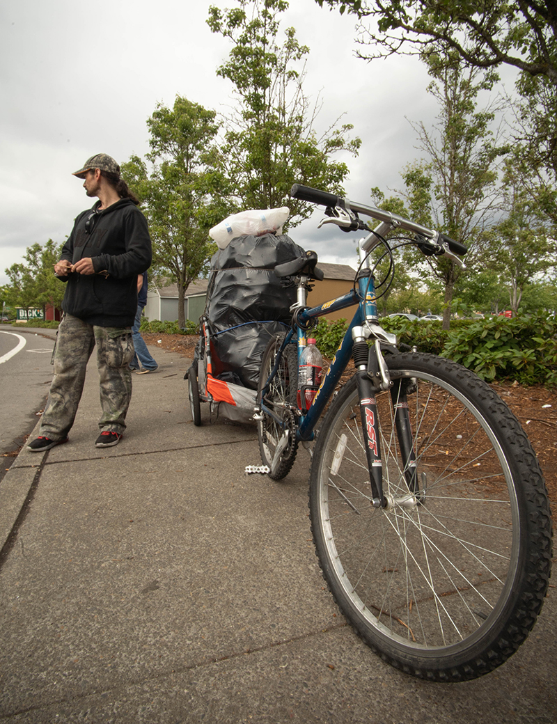 A man stands beside his bike. A cart attached to the bike is filled with several bags of recyclables stacked high.