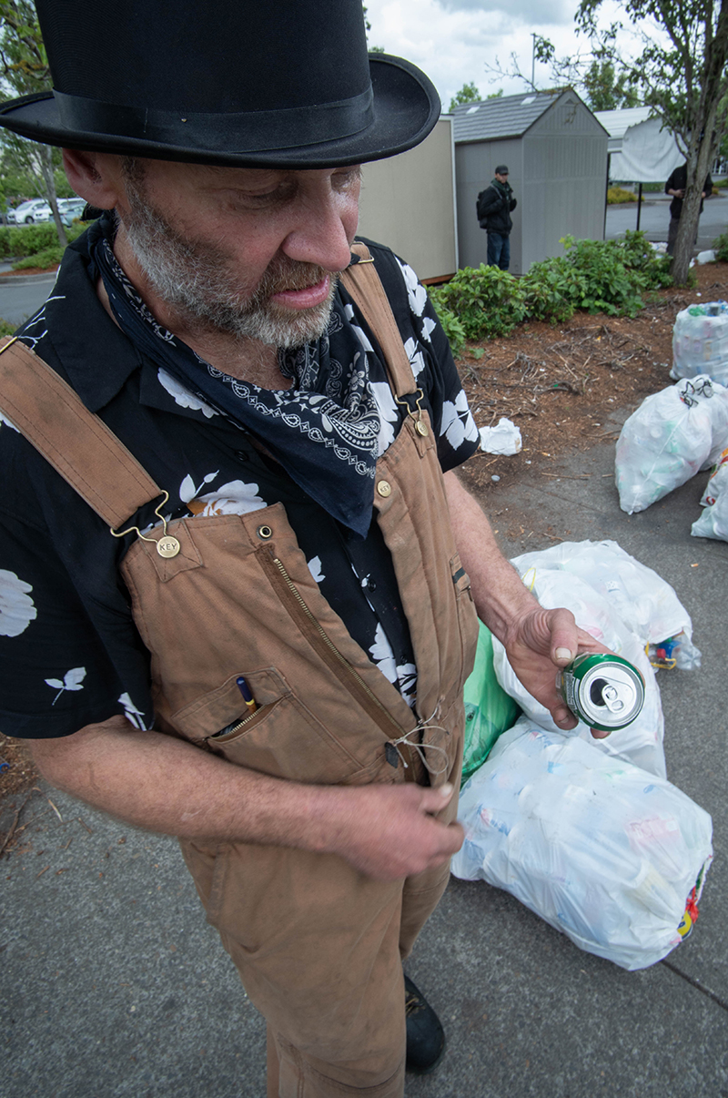 A man holds an aluminum can. Garbage bags full of recyclables lay on the ground beside him.