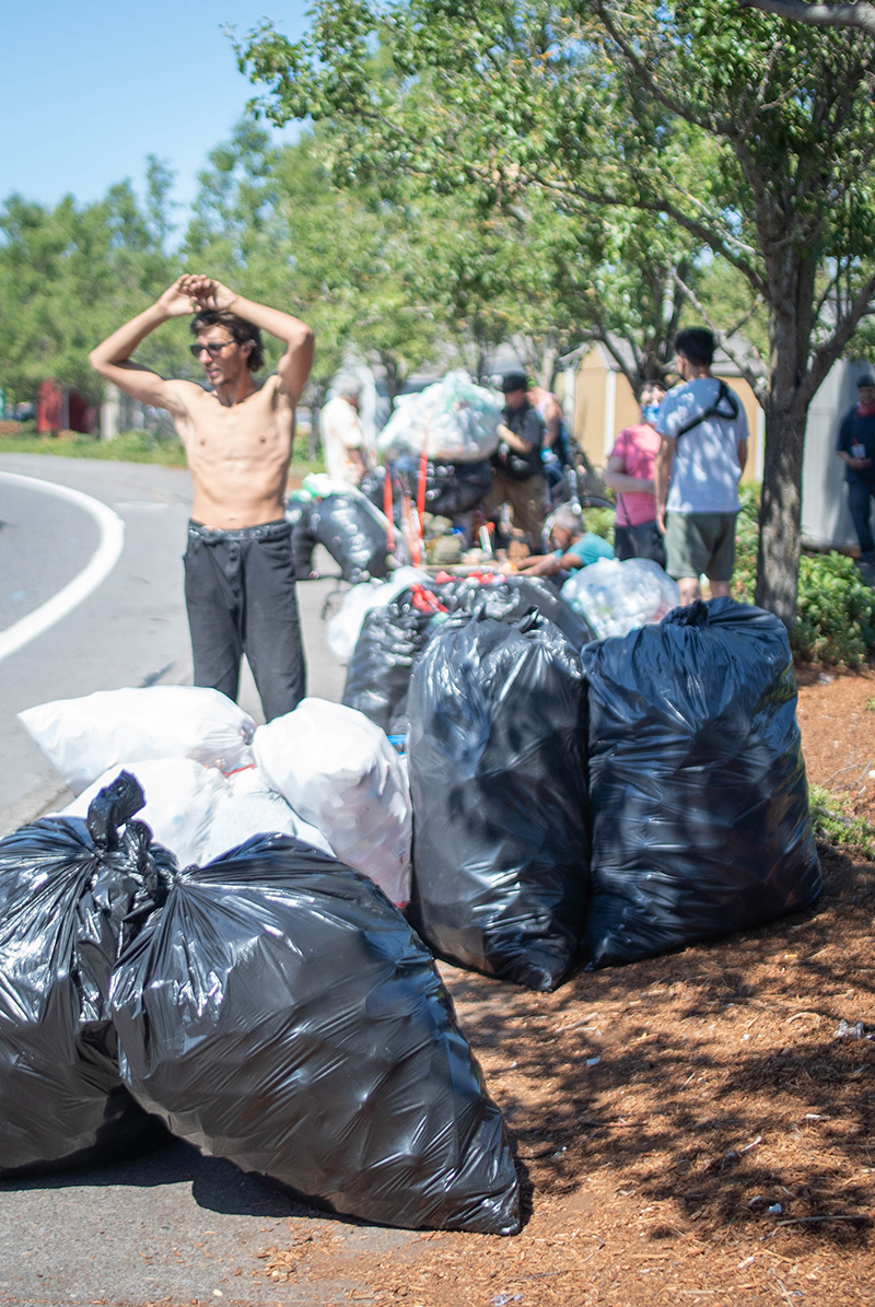 A shirtless man stands along the side of the road, in front of other people. At least a dozen bags full of recyclables are on the ground beside him or in carts behind him.