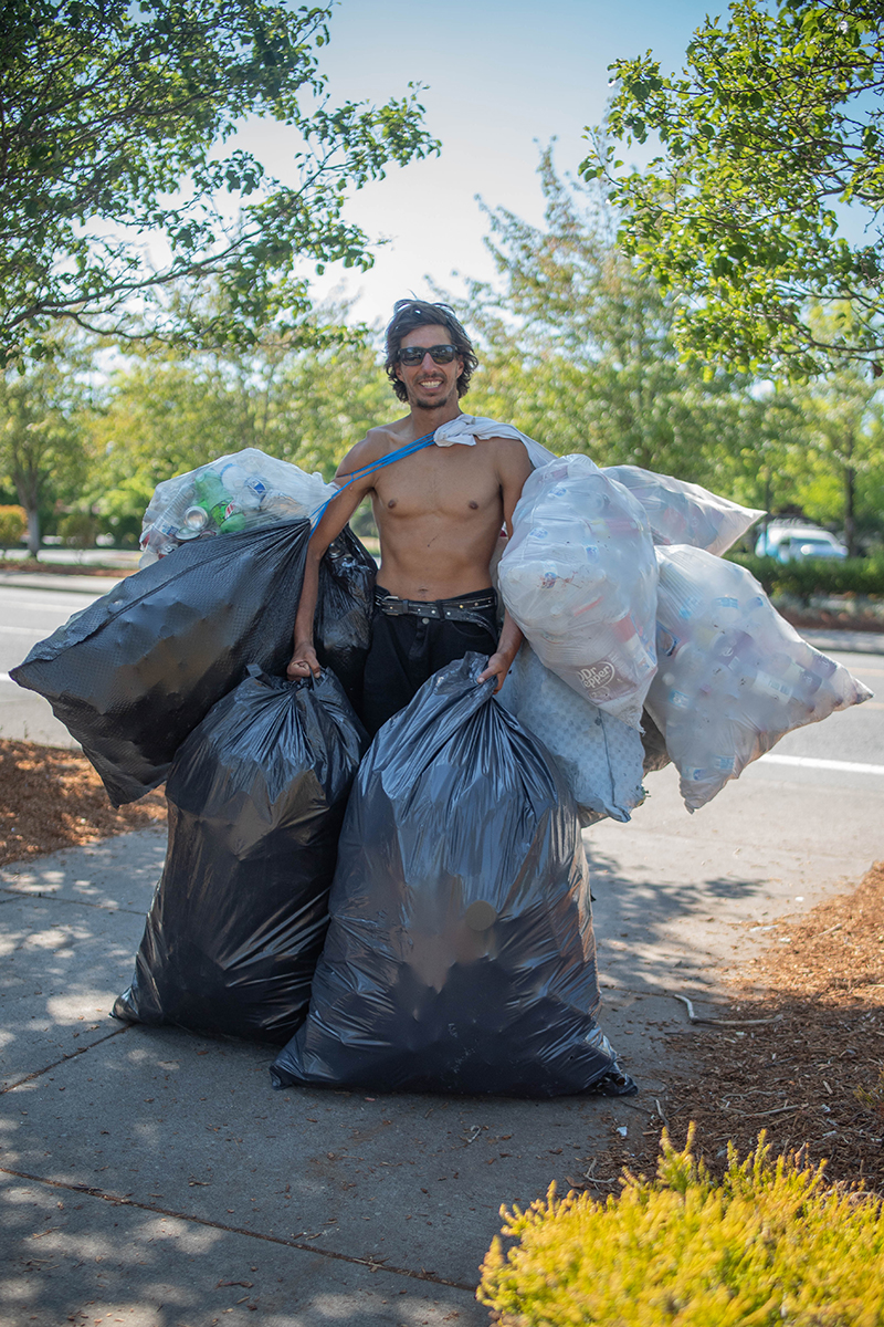 A man holds up at least eight garbage bags full of recyclable containers.