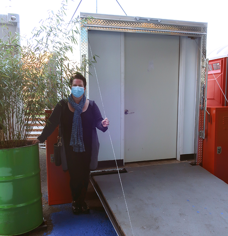 Sandra Comstock wears a face covering, standing outside a large trailer
