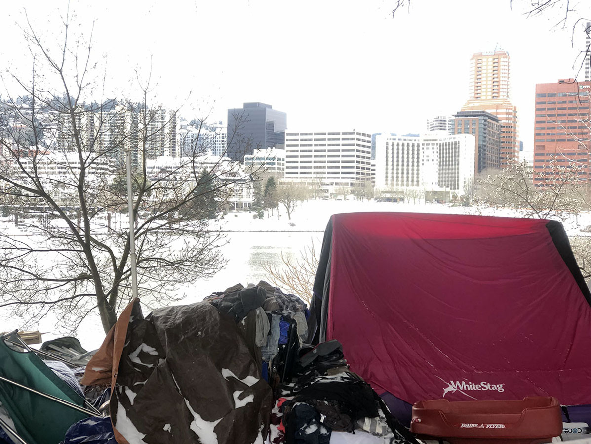 Tents surrounded by snow in front of the Portland skyline