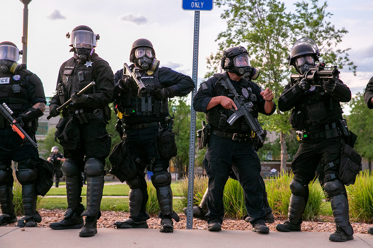 Police stand shoulder-to-shoulder in riot gear