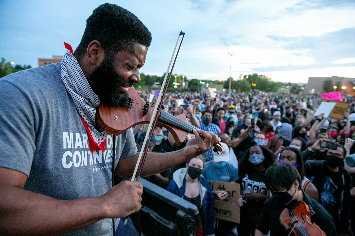 Jeff Hughes plays his violin, surrounded by a crowd