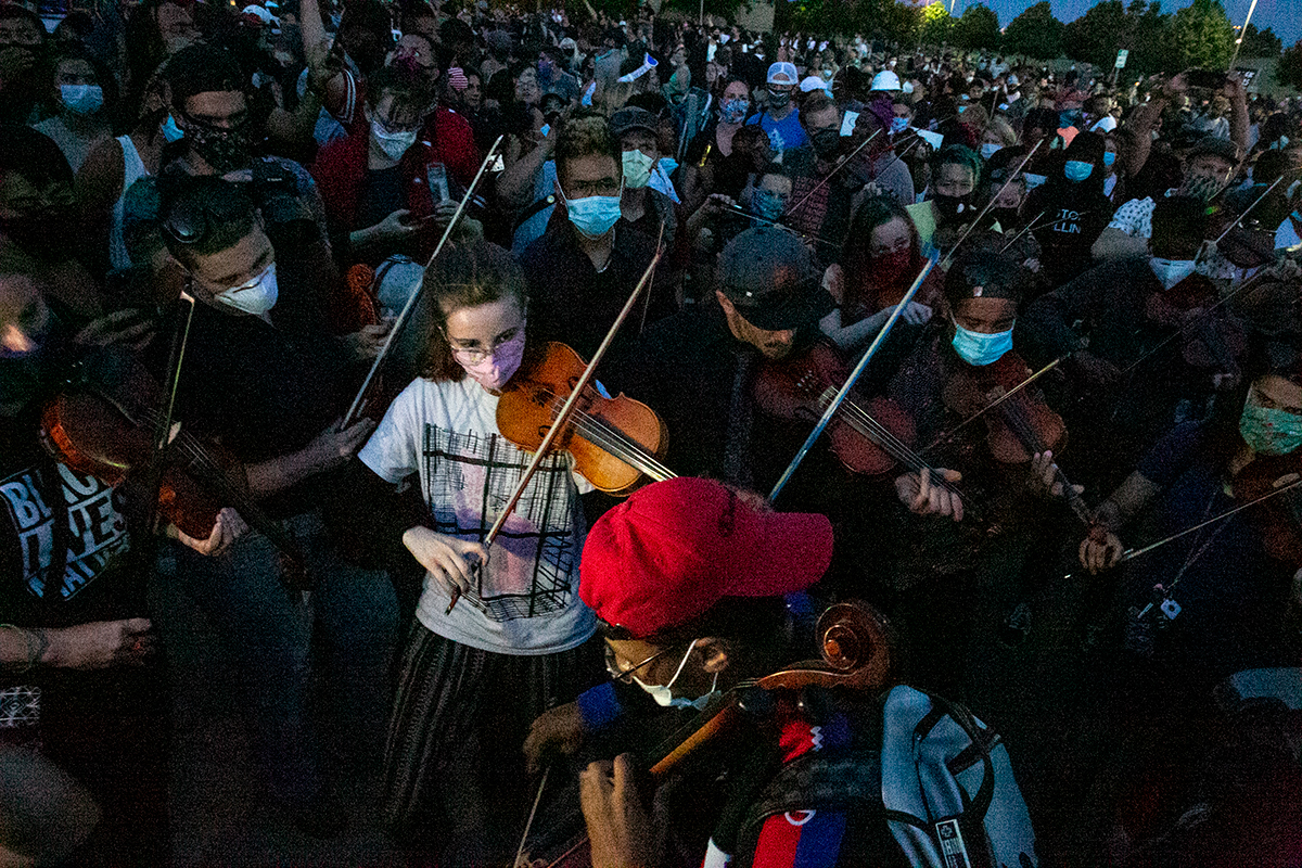 A large group of violinists wearing protective masks plays together