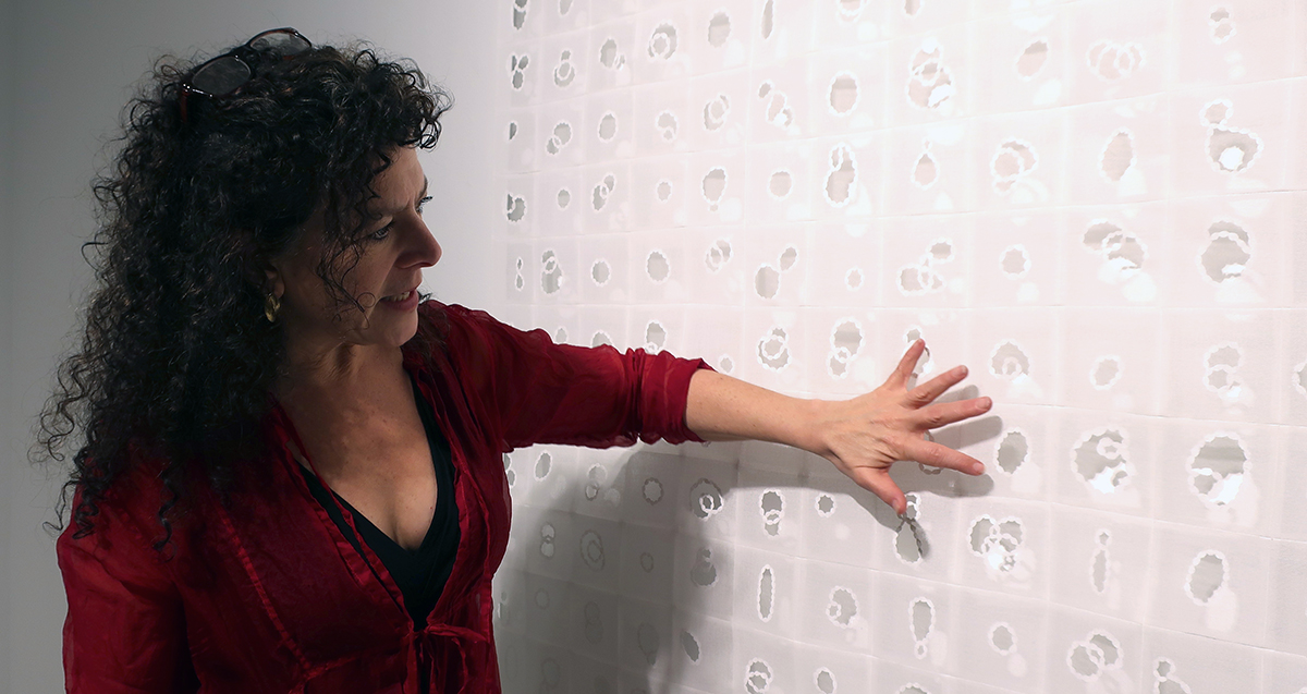 Dana Lynn Louis points to the detail in a large woven piece of art