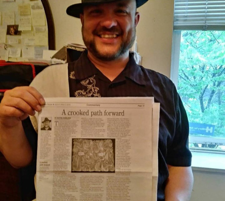 Dustin Dandliker holds up a Street Roots newspaper