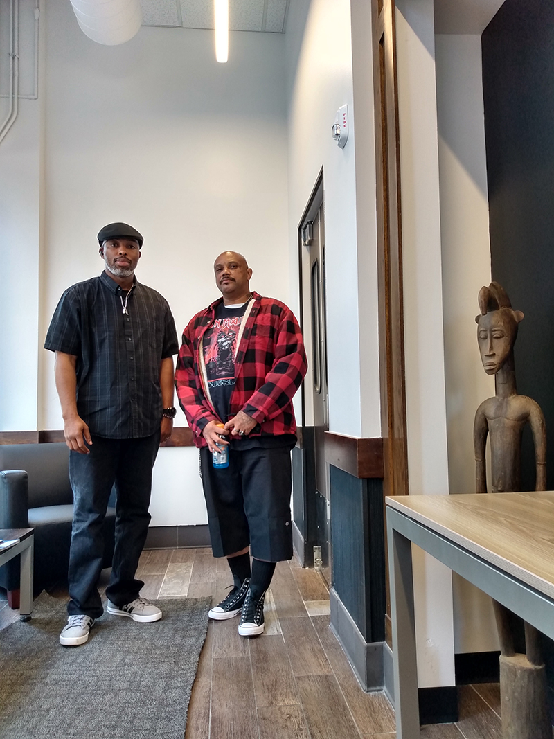 Patrick Alexander and Richard Holmes stand near an African statue at the new Flip the Script space