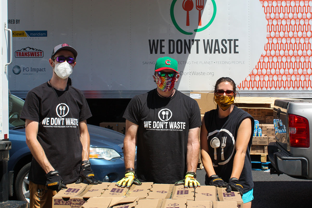 Volunteers wear We Don't Waste T-shirts and protective masks