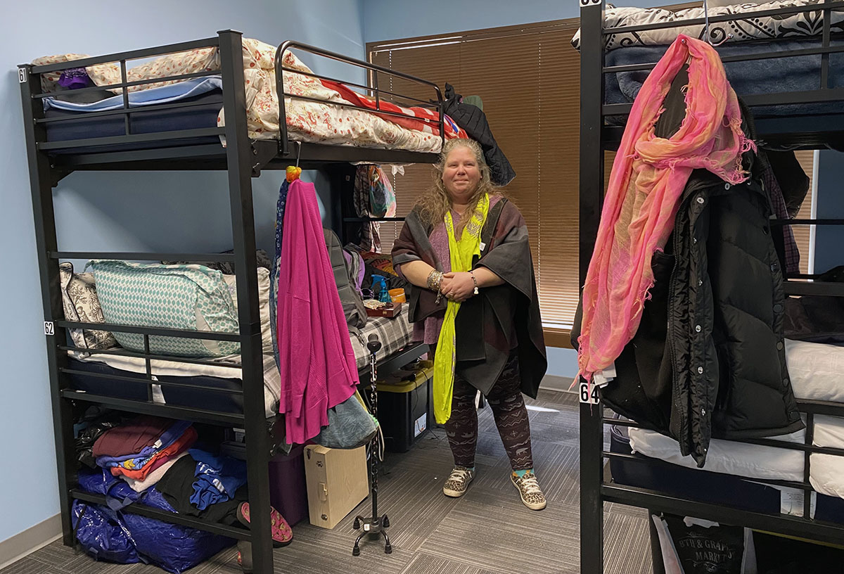 Elise Johnson stands beside bunk beds in a room at Kelly Shelter