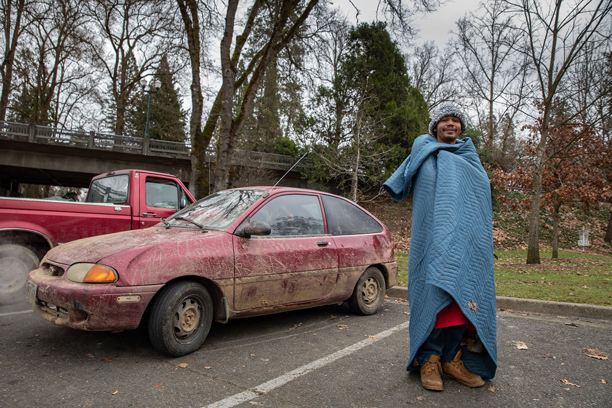 Wrapped in a furniture pad, Sam Walker stands next to a car.