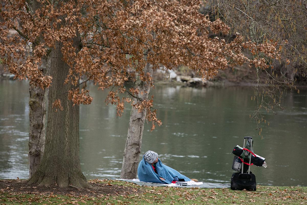 Sam Walker rests by the river. His belongings sit beside him.