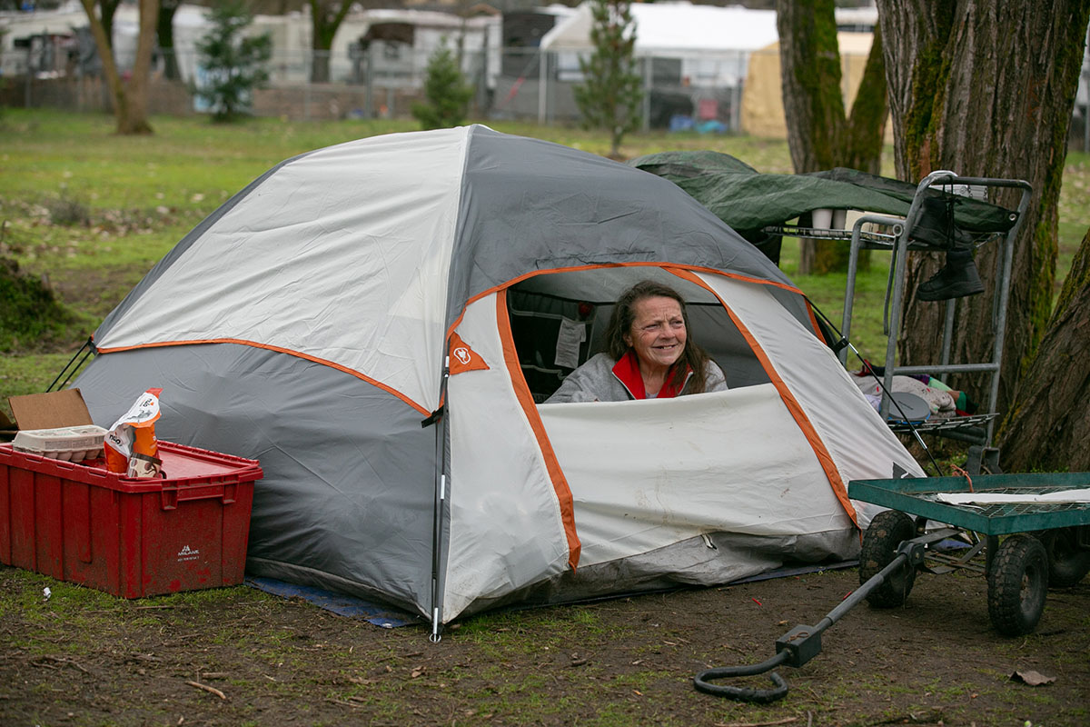 Dolores Nevin peers out from inside of her tent at Riverside Park