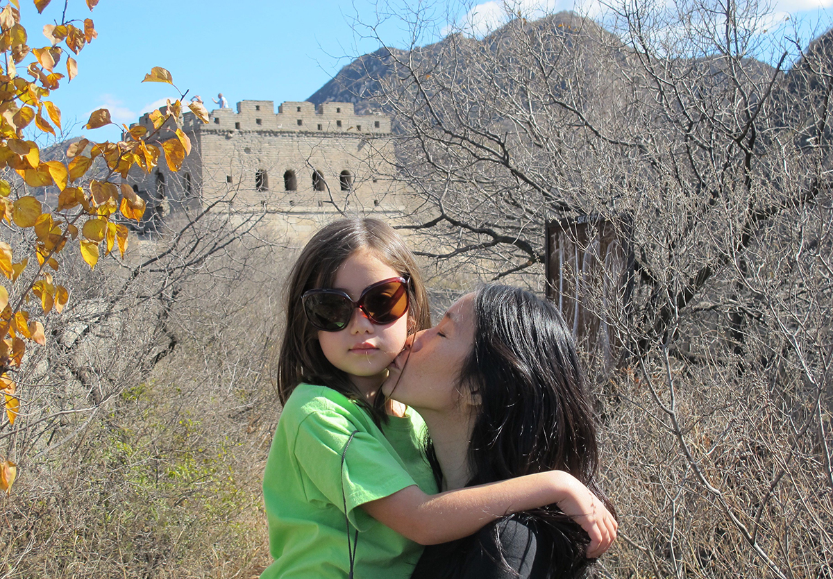 Lan Cao holds Harlan, who was a child, with the Great Wall of China in the background.