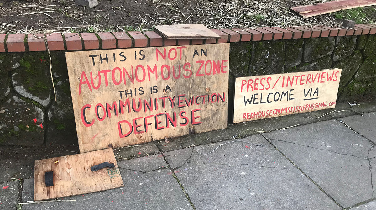 Signs read: This is not an autonomous zone, this is a community eviction defense. Press/interviews welcome via redhouseonmississippi@gmail.com