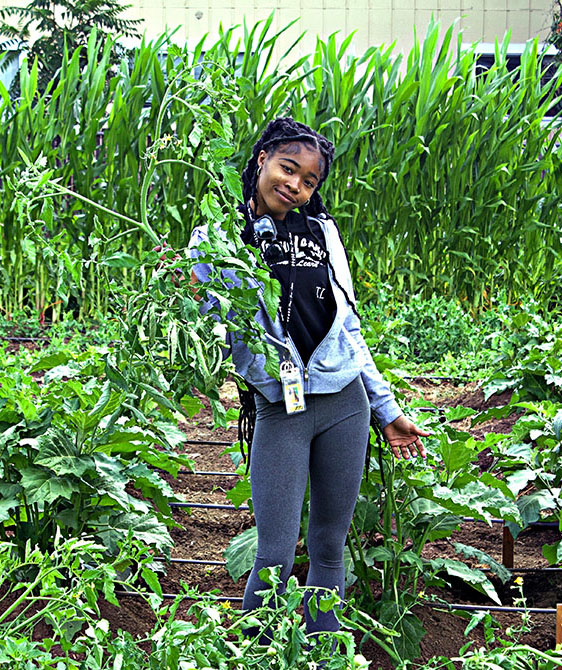 Photo of Justice Hudson working in the community garden.