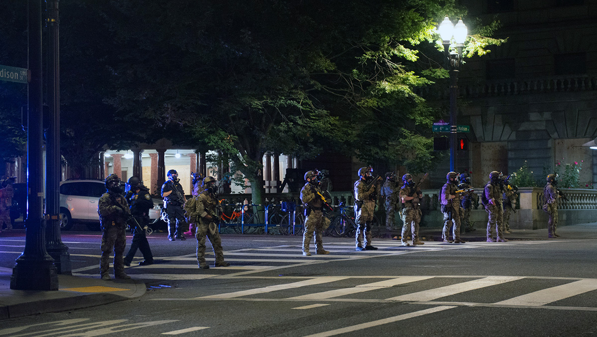 Federal police line up across a street in downtown Portland.