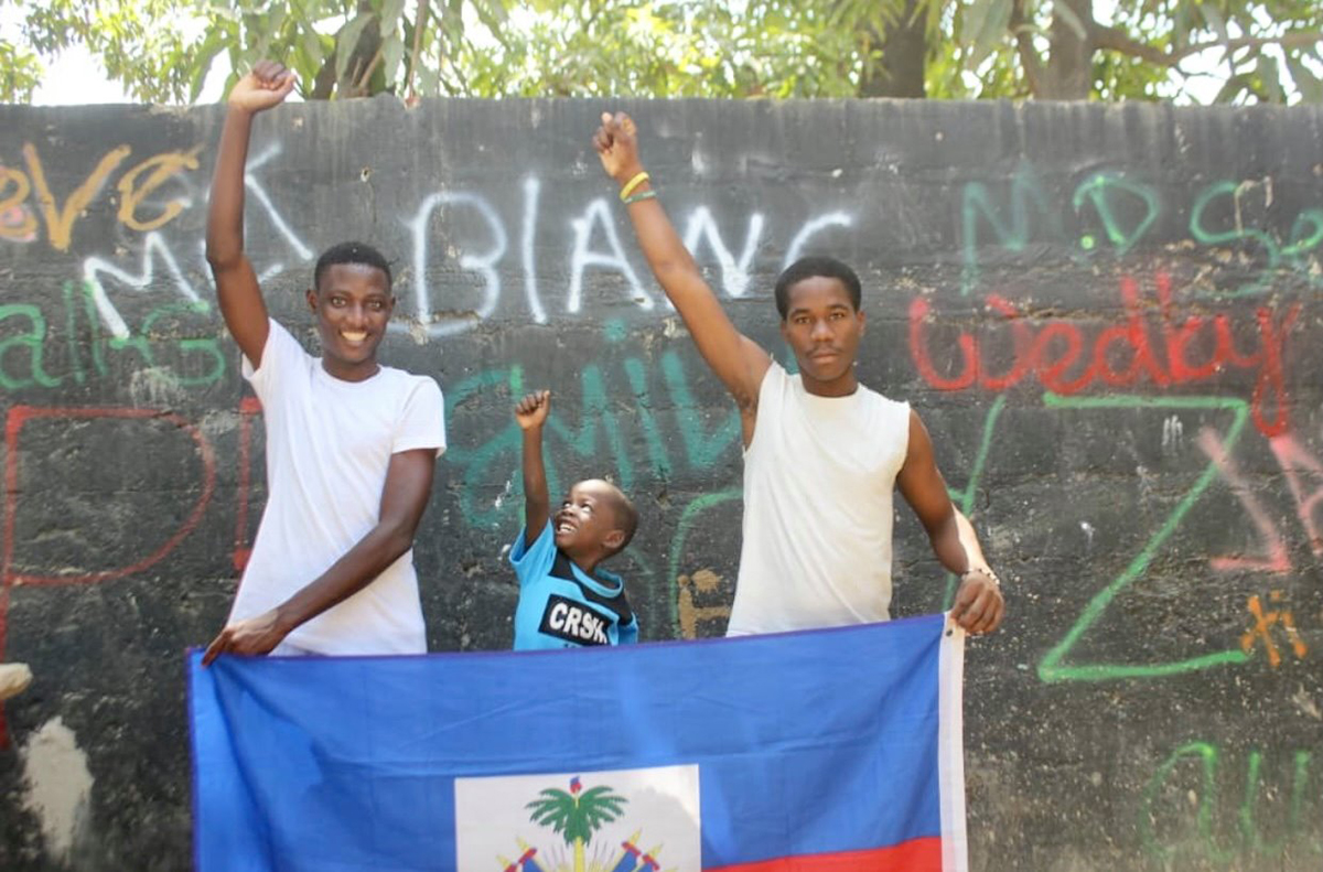 Two older boys and a younger boy raise their fists, holding up the flag of Haiti