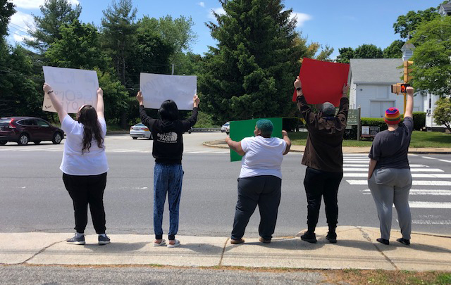 Youths hold up signs alongside the road