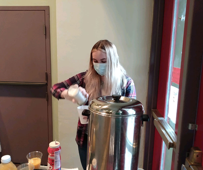 Photo of Elizabeth Prater pouring sugar into a cup at St. André Bessette