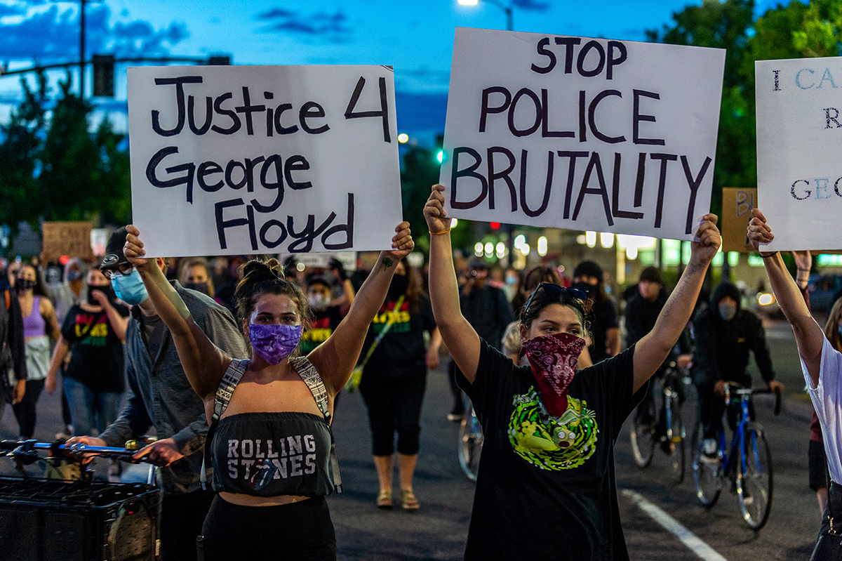 Protesters hold signs: Justice for George Floyd. Stop police brutality.